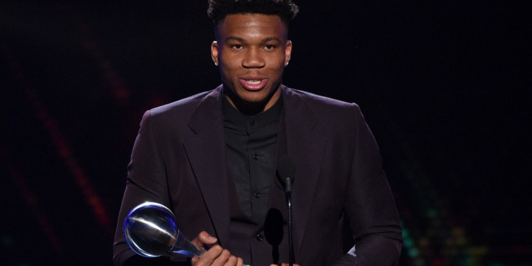 "Giannis Antetokounmpo holding and award for America's ""Athlete of the year"""